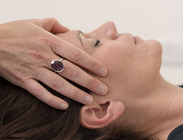 A picture of a client receiving reiki to her head