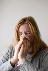 A picture of a women blowing her nose