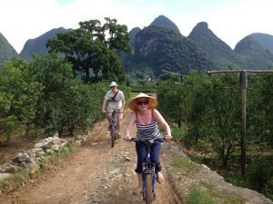 a picture of a woman and man riding bikes in the hills of China