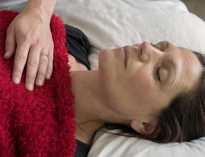 A picture of a women having a reiki treatment. The practitioners hands are on her chest.