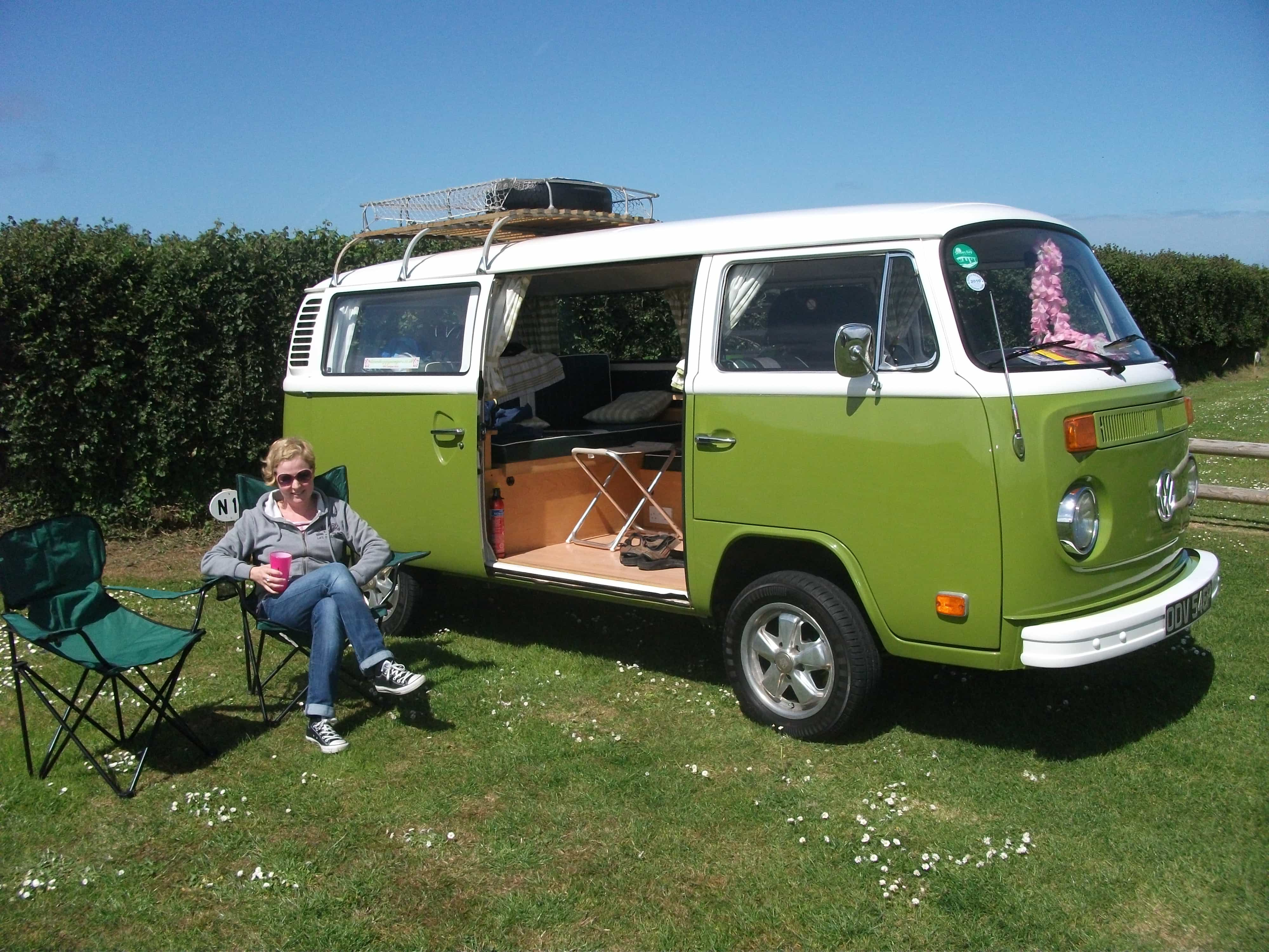 practitioner on her summer holidays sitting on a camping chair beside a 1970's VW Campervan