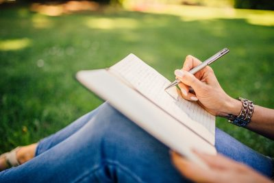 woman sitting outside on the grass writing in her journal